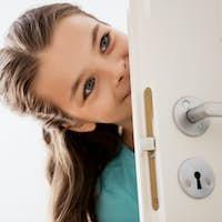happy smiling beautiful girl behind door at home
