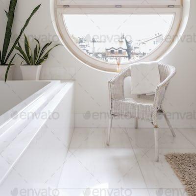 Spacious white bathroom with round window
