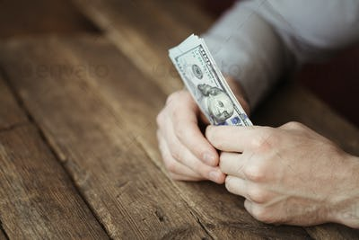 Male hands holding dollar banknote on old wooden background