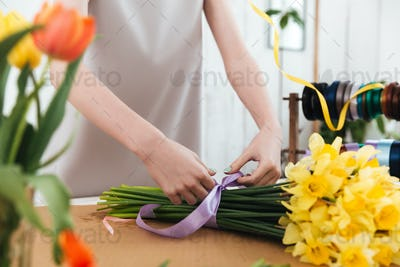 Cropped image of woman florist using ribbon to bandage bouquet