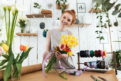 Young pretty woman looking camera while collecting bouquet in workshop