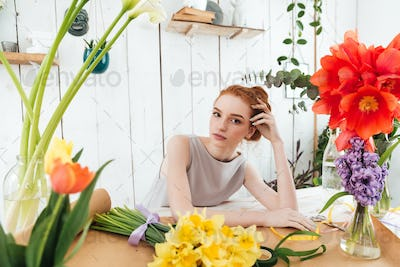 Tired young woman florist gazing at camera while working