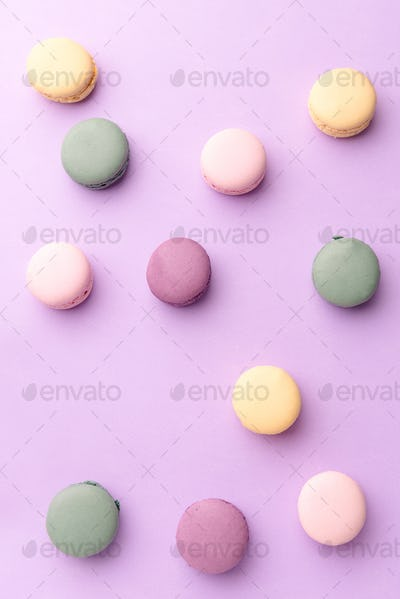 Sweet colorful macaroons on purple table background.