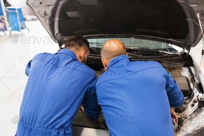 mechanic men repairing car at workshop