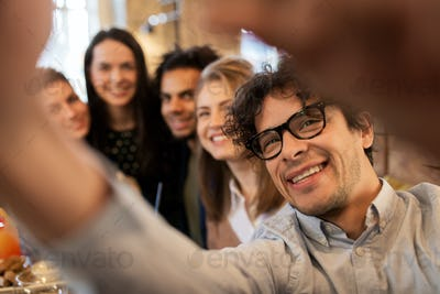 happy man taking selfie with friends at restaurant