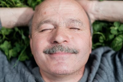 Mature Happy Man Lying On Green Grass. He smiles and closes eyes.