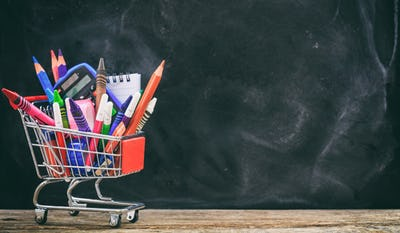 School shopping cart on blackboard background