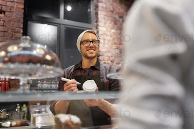 man or barman with coffee cup and customer at cafe