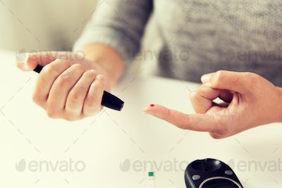 close up of woman making blood test by glucometer