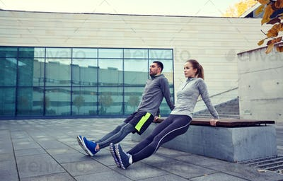 couple doing triceps dip exercise outdoors