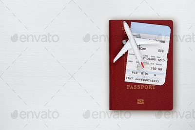 Passport, boarding pass and toy airplane on table top view