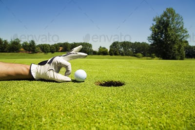 Golf Player Cheating Putting Ball Into Hole With Hand