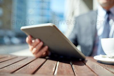 businessman with tablet pc and coffee outdoors