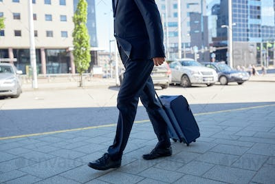 senior businessman walking with travel bag in city