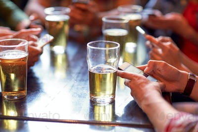 friends with beer and smartphones at bar or pub