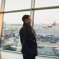 Travel concept with young man in airport interior with city view and a plane flying by.
