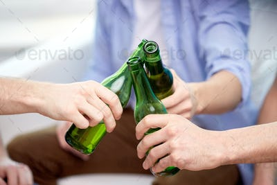 close up of friends clinking beer bottles at home