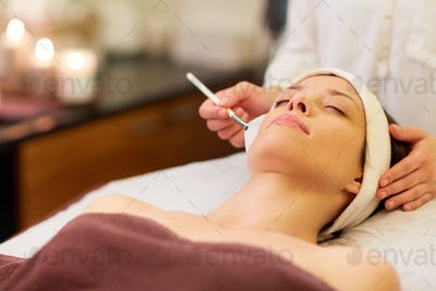 beautician applying facial mask to woman at spa