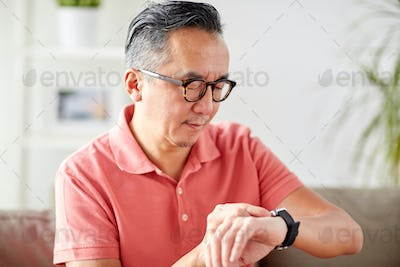 asian man checking time on wristwatch at home