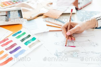 Female fashion designer working on sketches with paint