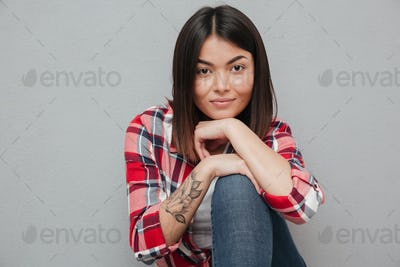 Smiling young asian woman isolated over grey wall