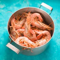 Big shrimps in the metal pot on the background