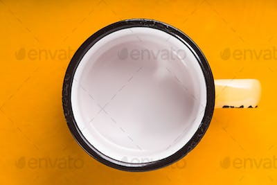 Empty enameled cup on the yellow background