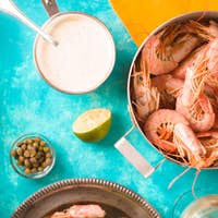 Prawns and savory sauce on the cyan background