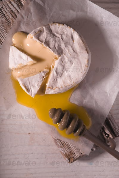 Brie cheese with honey on the white wooden table