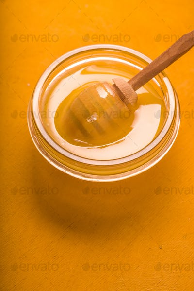 Honey on the glass bowl on the yellow background