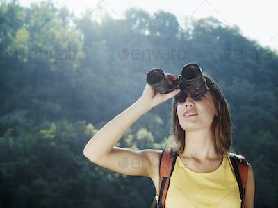 Young Woman Hiking On Mountain With Binoculars