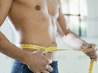 Man Measuring Belly And Waist With Yellow Tape