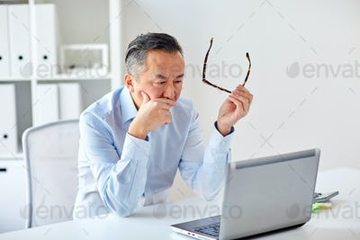 businessman with eyeglasses and laptop at office