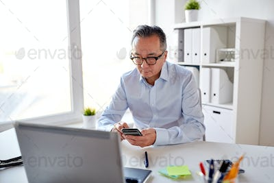 businessman with laptop texting on smartphone