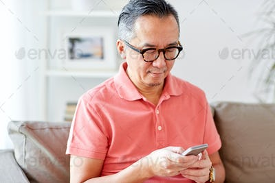 man with smartphone sitting on sofa at home