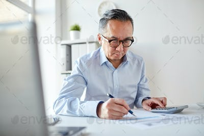businessman with calculator and papers at office