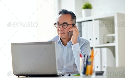 businessman with laptop calling on smartphone