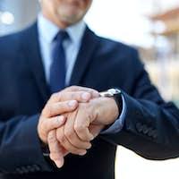 senior businessman with wristwatch on city street