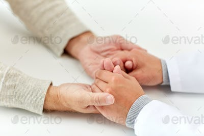 close up of doctor holding old man hand