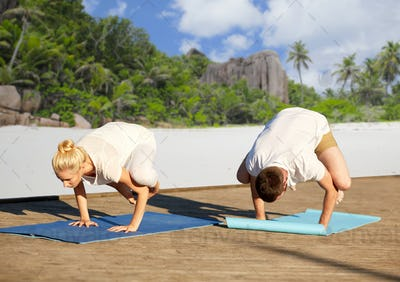 couple making yoga crow pose over tropical beach