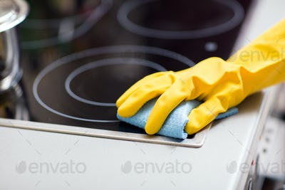 hand with rag cleaning cooker at home kitchen