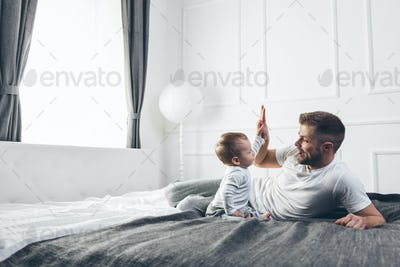Happy father with his son playing at home on the bed