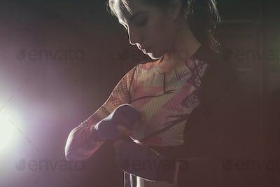 Female fighter putting on boxing gloves prepairing for training