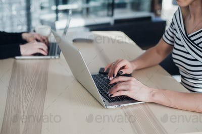Close up picture of hands of two businesswomen typing on their tablet computer and laptop.