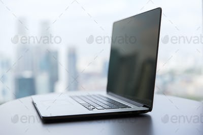 laptop computer with black screen on office table