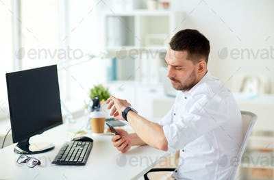 businessman with smartphone and computer at office
