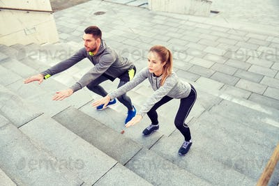 couple doing squats on city street stairs