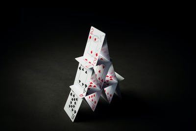 house of playing cards over black background