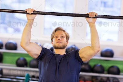 man exercising on bar and doing pull-ups in gym