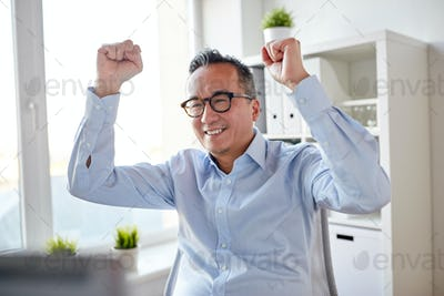 happy businessman celebrating victory at office